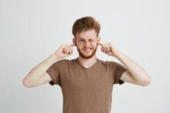 El retrato de jóvenes descontentó al hombre enojado con los oídos cerrados de la barba sobre el fondo blanco Foto de archivo