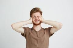 El retrato de jóvenes descontentó al hombre enojado con los oídos cerrados de la barba sobre el fondo blanco Fotografía de archivo libre de regalías