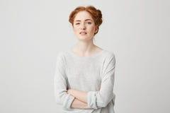 El retrato de jóvenes descontentó a la muchacha del jengibre que miraba la cámara con los brazos cruzados sobre el fondo blanco Imagen de archivo libre de regalías