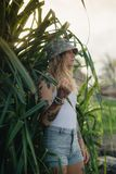 El retrato de jóvenes hermosos tatuó a la mujer sonriente que se colocaba en arbusto frondoso verde Fotos de archivo