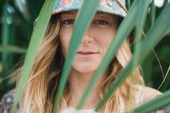 El retrato de jóvenes hermosos tatuó a la mujer sonriente que se colocaba en arbusto frondoso verde Foto de archivo
