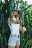 El retrato de jóvenes hermosos tatuó a la mujer sonriente que se colocaba en arbusto frondoso verde Imagen de archivo libre de regalías