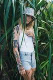 El retrato de jóvenes hermosos tatuó a la mujer sonriente que se colocaba en arbusto frondoso verde Foto de archivo libre de regalías
