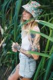 El retrato de jóvenes hermosos tatuó a la mujer sonriente que se colocaba en arbusto frondoso verde Imágenes de archivo libres de regalías