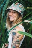 El retrato de jóvenes hermosos tatuó a la mujer sonriente que se colocaba en arbusto frondoso verde Imagen de archivo