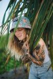 El retrato de jóvenes hermosos tatuó a la mujer sonriente que se colocaba en arbusto frondoso verde Imagenes de archivo