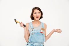 El retrato de jóvenes sorprendió a la muchacha hermosa, sosteniendo el martillo, lo Foto de archivo libre de regalías