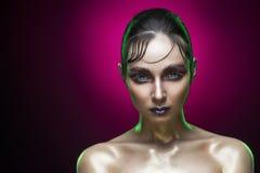 El retrato de la belleza de la mujer joven con un brillo mojado exacto del peinado y de la vanguardia construye en un fondo rojo  imagen de archivo libre de regalías