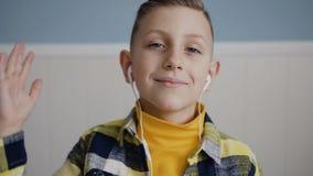 El retrato de la cara del blonde encantador del muchacho con los ojos azules que escucha la música en los auriculares mira almacen de metraje de vídeo