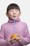 El retrato de la chica joven con explosiones y observa cerrado bebiendo una naranja con una paja, tiro del estudio Foto de archivo