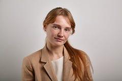 El retrato de la chica joven con el pelo del jengibre se vistió en chaqueta beige casual Fotos de archivo libres de regalías