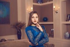 El retrato de la chica joven en el aparment del hotel vistió el vestido azul clásico Fotos de archivo libres de regalías