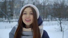 El retrato de la chica joven de risa en invierno caliente viste en el parque en invierno metrajes