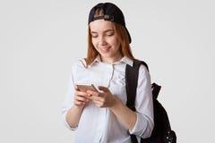 El retrato de la colegiala satisfecha juega al juego en línea en el teléfono elegante durante rotura en la escuela, aislada en el Foto de archivo libre de regalías