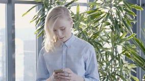 El retrato de la empresaria joven está mecanografiando el mensaje en su smartphone mientras que camina en el pasillo soleado, cám almacen de metraje de vídeo