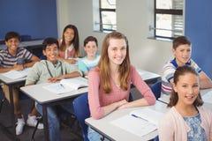 El retrato de la escuela sonriente embroma sentarse en sala de clase Imagen de archivo