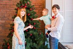 El retrato de la familia de la Navidad en la sala de estar casera del día de fiesta, casa que adorna por el árbol de Navidad mira Imagen de archivo