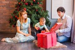 El retrato de la familia de la Navidad en la sala de estar casera del día de fiesta, casa que adorna por el árbol de Navidad mira Fotografía de archivo libre de regalías