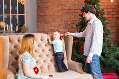 El retrato de la familia de la Navidad en la sala de estar casera del día de fiesta, casa que adorna por el árbol de Navidad mira Imagenes de archivo