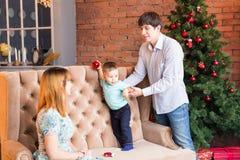 El retrato de la familia de la Navidad en la sala de estar casera del día de fiesta, casa que adorna por el árbol de Navidad mira Imagen de archivo libre de regalías