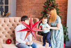 El retrato de la familia de la Navidad en la sala de estar casera del día de fiesta, casa que adorna por el árbol de Navidad mira Imágenes de archivo libres de regalías