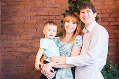 El retrato de la familia de la Navidad en la sala de estar casera del día de fiesta, casa que adorna por el árbol de Navidad mira Fotos de archivo