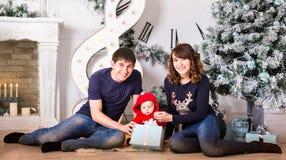 El retrato de la familia de la Navidad en la sala de estar casera del día de fiesta, actual caja de regalo, casa que adorna por e Imágenes de archivo libres de regalías
