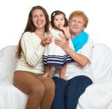 El retrato de la familia en el fondo blanco, gente feliz se sienta en el sofá Niños con la madre y la abuela Fotos de archivo libres de regalías