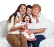 El retrato de la familia en el fondo blanco, gente feliz se sienta en el sofá Niños con la madre y la abuela Foto de archivo libre de regalías
