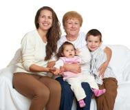 El retrato de la familia en el fondo blanco, gente feliz se sienta en el sofá Niños con la madre y la abuela Imagen de archivo
