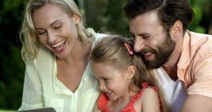 El retrato de la familia linda está mirando un ordenador portátil y una sonrisa almacen de video