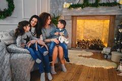 El retrato de la familia de la Navidad de la sonrisa feliz mima a abrazar a sus niños cerca a la chimenea adornada con el abeto y Fotografía de archivo libre de regalías