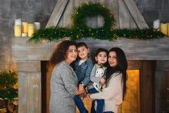 El retrato de la familia de la Navidad de la sonrisa feliz mima a abrazar a sus niños cerca a la chimenea adornada con el abeto y Fotografía de archivo