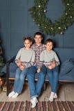 El retrato de la familia, papá con dos niños se está sentando en el sofá que sonríen en el cuarto adornado del Año Nuevo foto de archivo