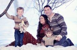 El retrato de la familia se sienta en fondo del bosque de la nieve del estudio Fotos de archivo