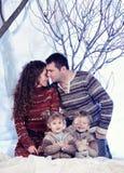El retrato de la familia se sienta en fondo del bosque de la nieve del estudio Fotografía de archivo libre de regalías
