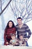El retrato de la familia se sienta en fondo del bosque de la nieve del estudio Foto de archivo