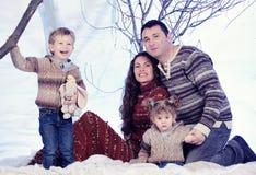 El retrato de la familia se sienta en fondo del bosque de la nieve del estudio Imágenes de archivo libres de regalías