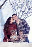 El retrato de la familia se sienta en fondo del bosque de la nieve del estudio Foto de archivo libre de regalías