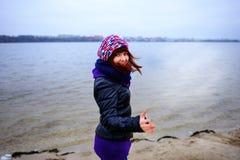 El retrato de la forma de vida de la mujer delgada caucásica joven corre a lo largo de otoño de la playa Foto de archivo libre de regalías