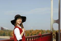 El retrato de la forma de vida del modelo elegante lleva el traje rojo, sombrero negro fotos de archivo libres de regalías