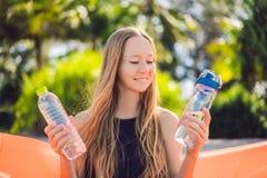 El retrato de la forma de vida del verano de la muchacha bonita que se sienta en el sof? inflable anaranjado selecciona una botel foto de archivo