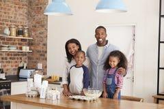 El retrato de la hornada de la familia se apelmaza en cocina junto imagen de archivo