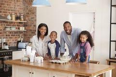 El retrato de la hornada de la familia se apelmaza en cocina junto fotografía de archivo