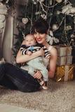 El retrato de la madre feliz y del pequeño bebé cerca adornó el árbol de navidad con los regalos Foto de archivo