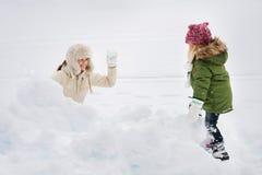El retrato de la madre feliz y el niño que juega la bola de nieve luchan Imágenes de archivo libres de regalías