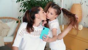 El retrato de la madre hermosa y su hija hacen el selfie en el teléfono, cámara lenta almacen de metraje de vídeo