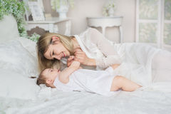 El retrato de la madre joven juega con su pequeño bebé en una cama Imagen de archivo