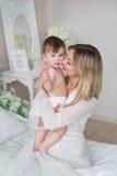 El retrato de la madre joven sonriente detiene a su pequeño bebé en las manos en un dormitorio Fotografía de archivo