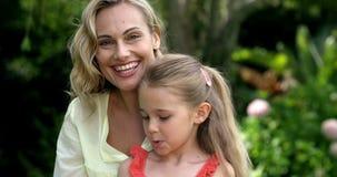 El retrato de la madre linda y la hija están mirando la cámara y la sonrisa almacen de video